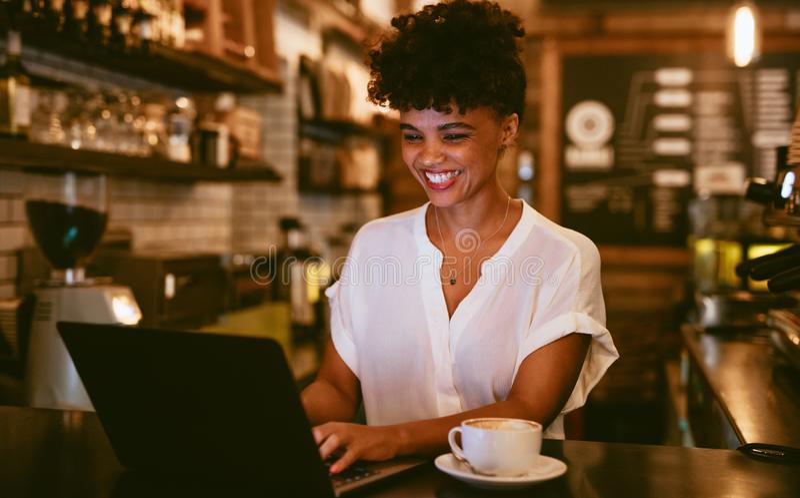 Glimlachende coffeeshop eigenaar die laptop met behulp van stock afbeelding