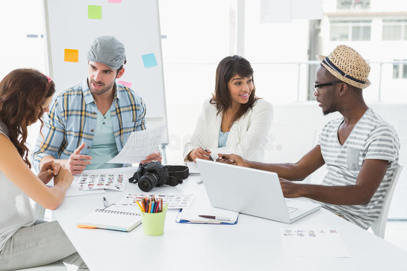 Glimlachende collega's die bij bureau het op elkaar inwerken zitten royalty-vrije stock foto's