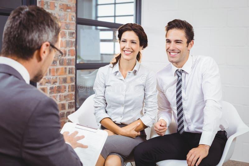 Glimlachende collega's die met bedrijfsberoeps bespreken royalty-vrije stock afbeelding