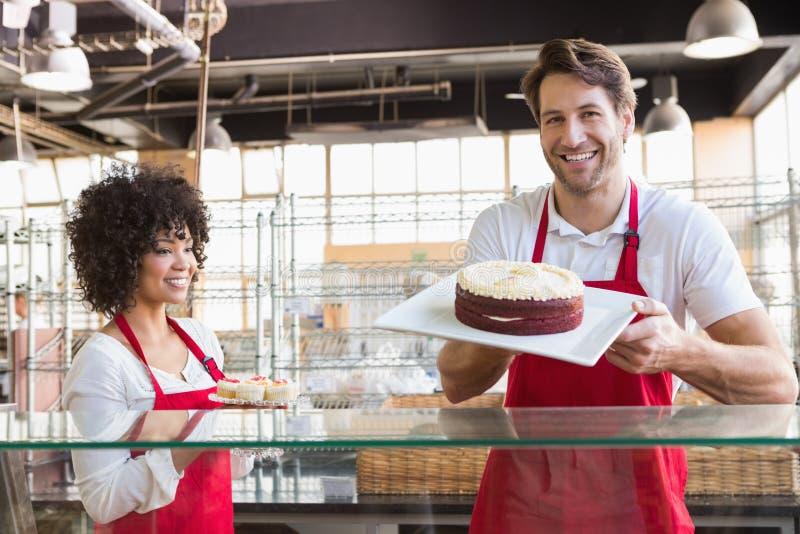 Glimlachende collega's in eenvormige tonende cakes stock fotografie