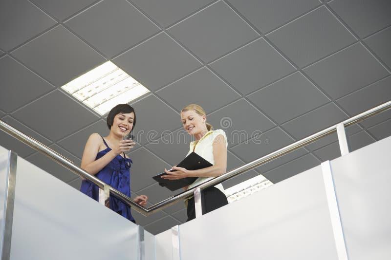 Glimlachende Collega's met Cellphone en Ontwerper stock afbeeldingen