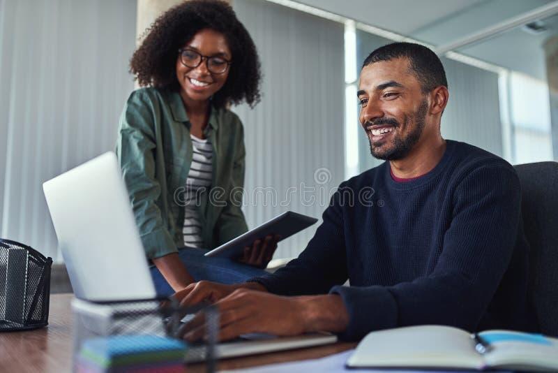 Glimlachende creatieve collega's die in het bureau samenwerken royalty-vrije stock afbeeldingen