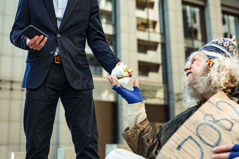 Glimlachende dakloze mens die hamburger van kind-hearted vreemdeling nemen stock afbeeldingen