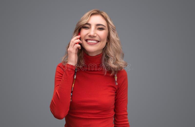 Glimlachende dame die in sweater op telefoon spreken royalty-vrije stock foto