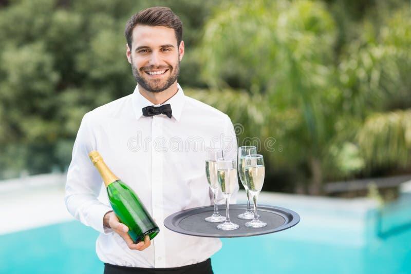 Glimlachende de champagnefluiten en fles van de kelnersholding stock foto