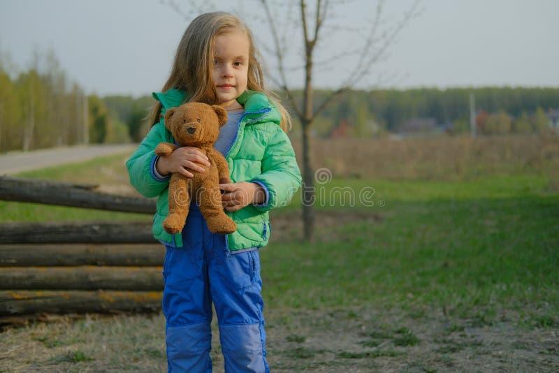 Glimlachende de holdingsteddybeer van het babymeisje in openlucht stock afbeelding