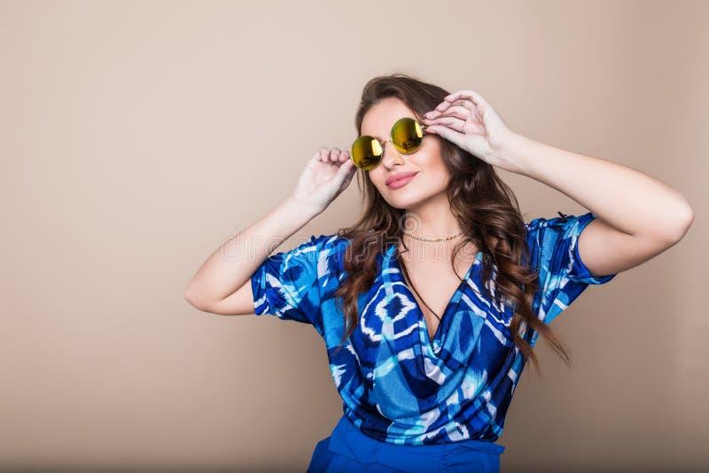 Glimlachende de zomervrouw met zonnebril over heldere achtergrond Studioschot, exemplaarruimte stock foto