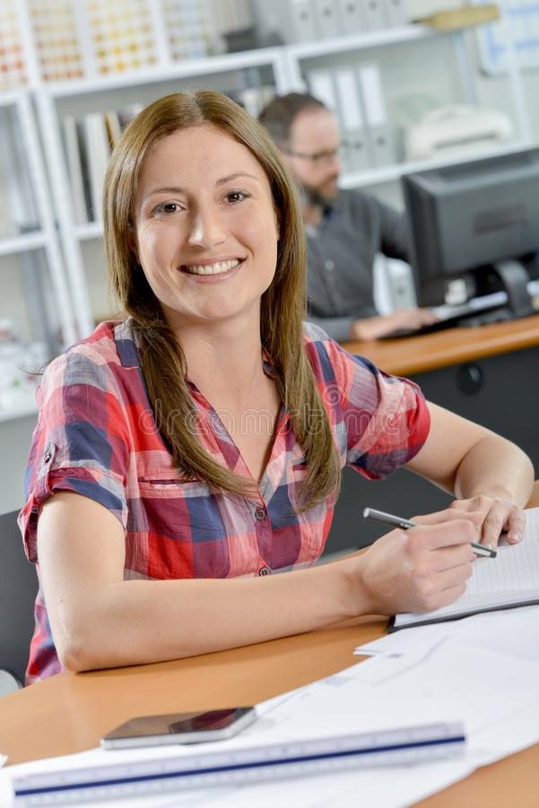 Glimlachende die dame bij bureau wordt gezeten royalty-vrije stock foto's