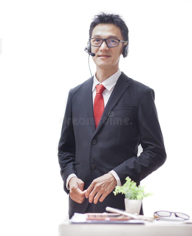 Glimlachende die mens in call centre met hoofdtelefoon op witte achtergrond wordt ge?soleerd Aziatische de mensenbespreking van h royalty-vrije stock foto's