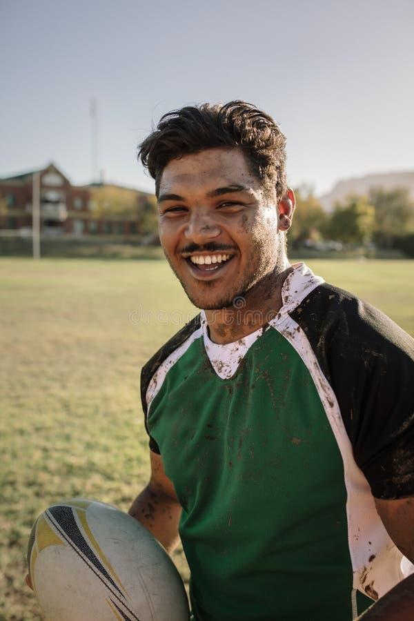 Glimlachende die rugbyspeler in modder wordt gesmeerd stock afbeeldingen