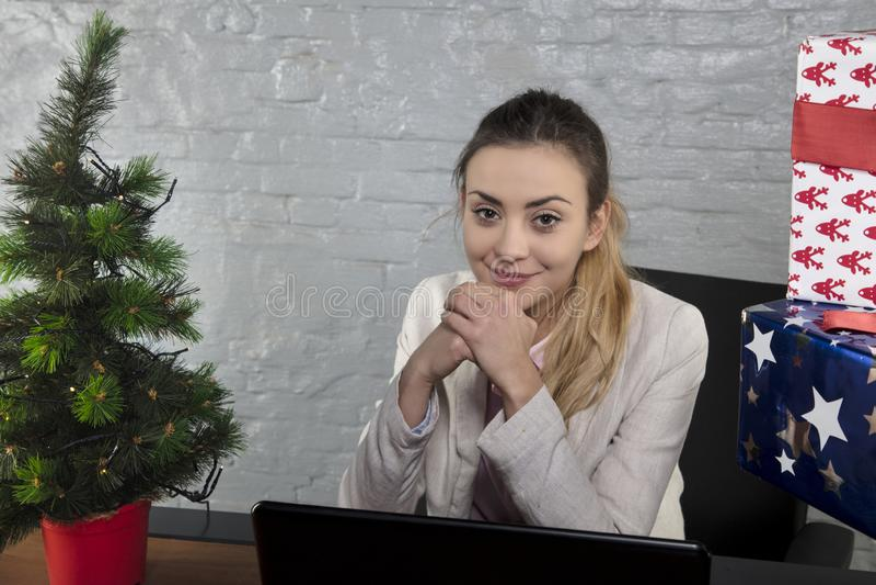 Glimlachende die secretaresse door Kerstmisgiften wordt omringd stock foto's