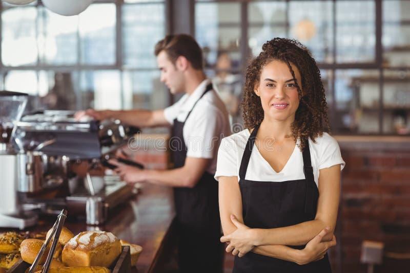 Glimlachende die serveerster met wapens voor collega worden gekruist stock afbeeldingen