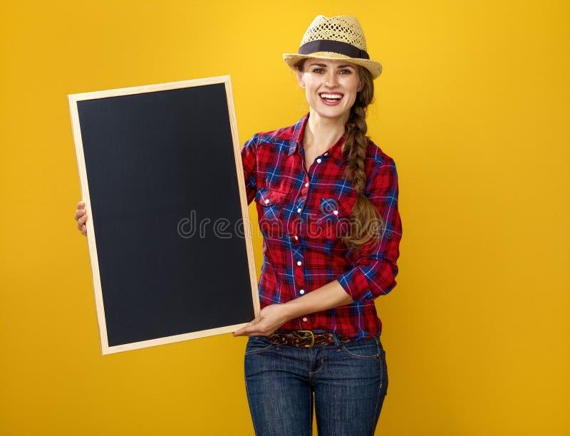 Glimlachende die vrouwenkweker op gele tonende lege raad wordt geïsoleerd royalty-vrije stock fotografie