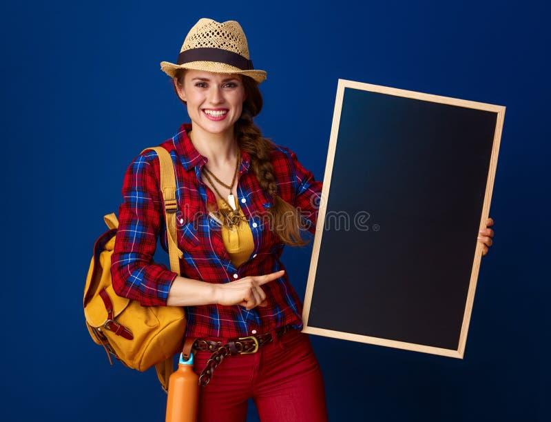 Glimlachende die vrouwenwandelaar op blauw wordt geïsoleerd die op lege raad richten stock fotografie
