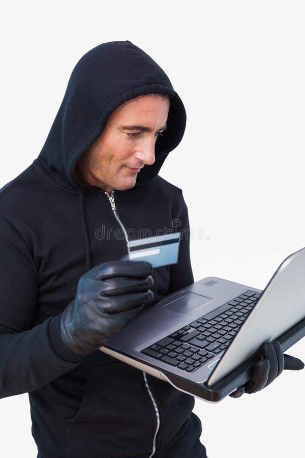 Glimlachende dief in kapjasje die laptop en creditcard gebruiken royalty-vrije stock afbeelding