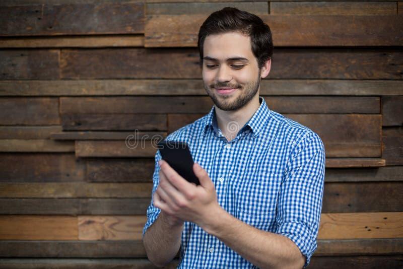 Glimlachende directeur die mobiele telefoon met behulp van royalty-vrije stock fotografie