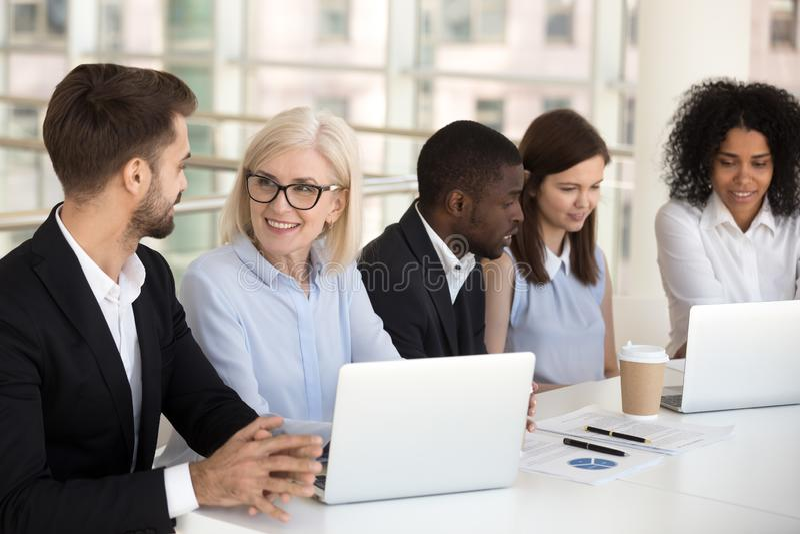 Glimlachende diverse collega's die bij laptop in bestuurskamer samenwerken royalty-vrije stock afbeeldingen