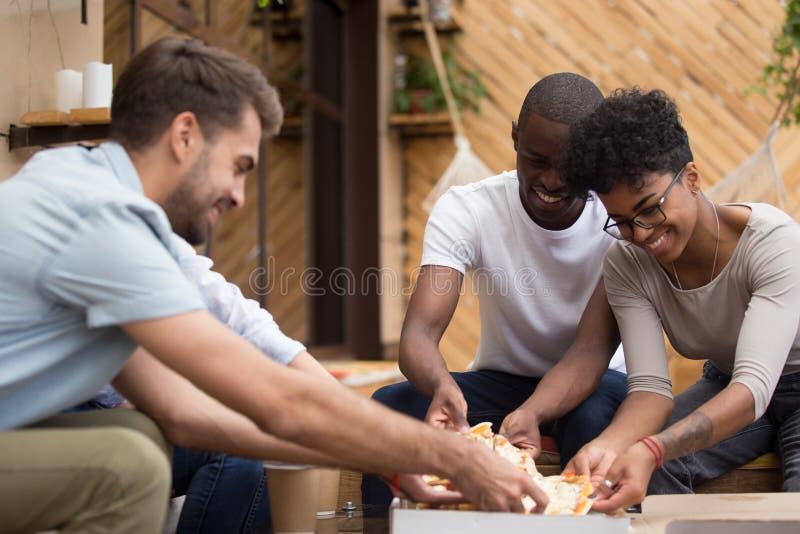 Glimlachende diverse multi-etnische vrienden die pizzaplakken van doos nemen stock afbeelding
