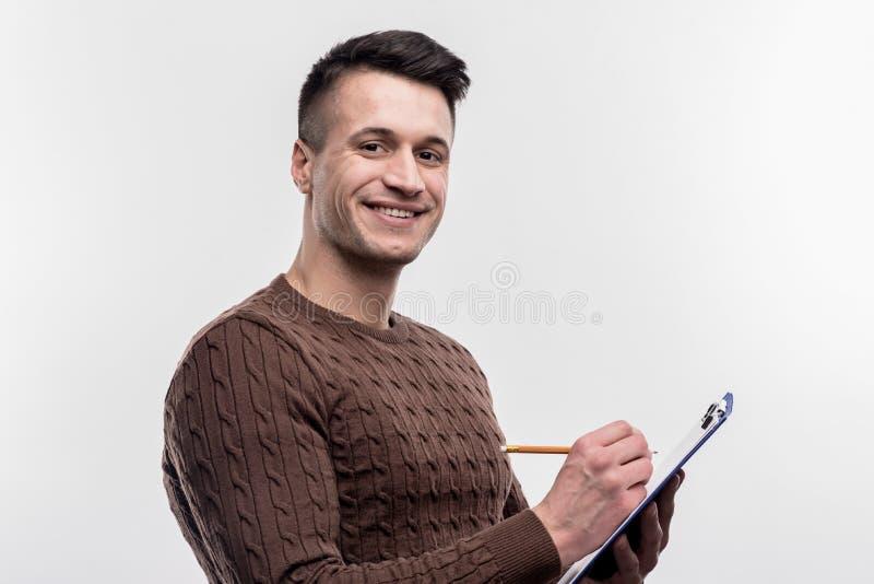 Glimlachende donker-haired mannelijke secretaresse die bruine sweater dragen die nota's maken royalty-vrije stock foto's