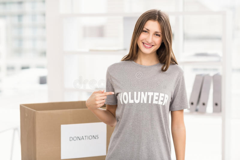 Glimlachende donkerbruine vrijwilliger die haar overhemd tonen royalty-vrije stock foto's