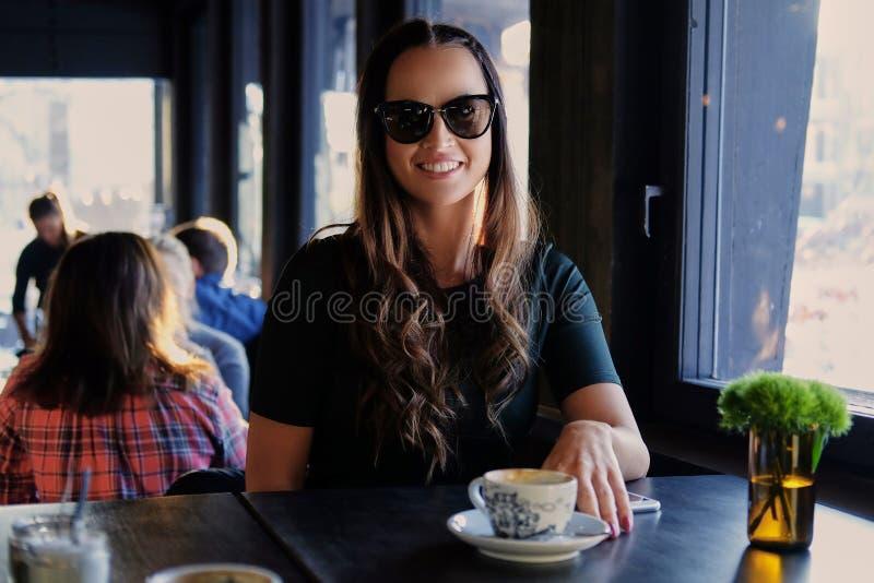 Glimlachende donkerbruine vrouw in een koffie royalty-vrije stock fotografie