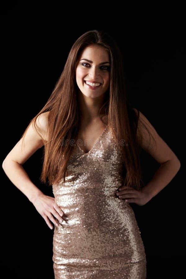 Glimlachende donkere haired vrouw in avondjurk, handen op heupen royalty-vrije stock fotografie