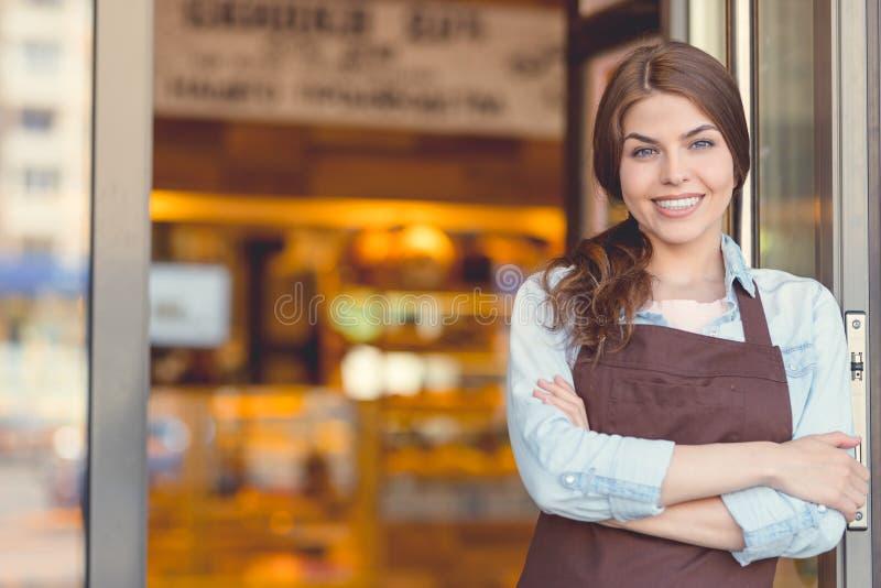 Glimlachende eigenaar in eenvormig in de bakkerij stock fotografie