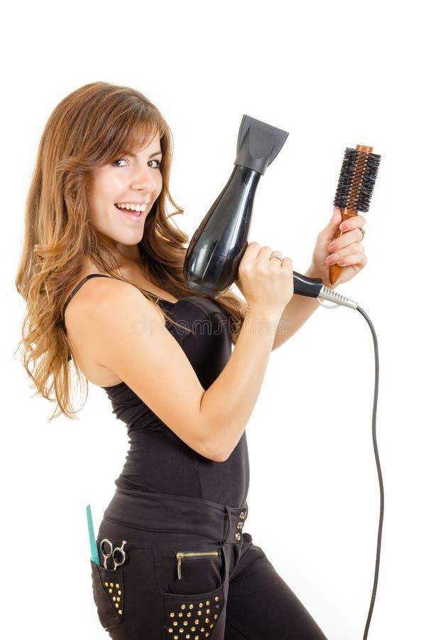 Glimlachende en gelukkige professionele Kaukasische donkerbruine vrouwelijke kapper stock afbeelding