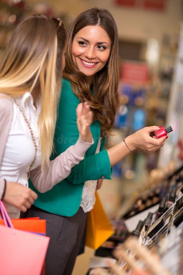 Glimlachende en vrouwen die schoonheidsmiddelen kopen kijken royalty-vrije stock afbeeldingen