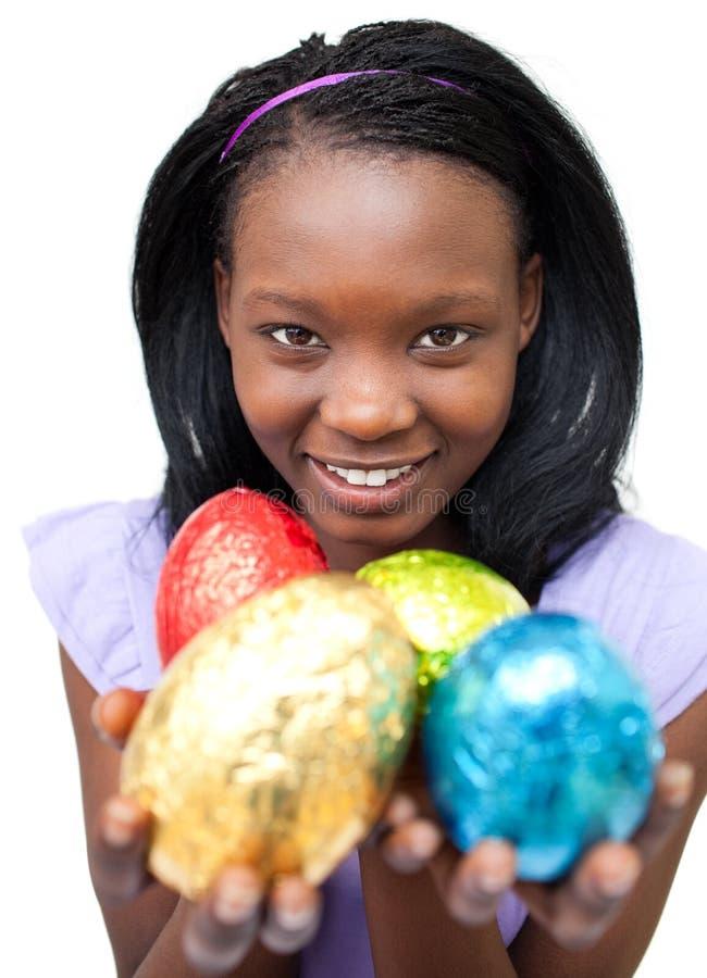 Glimlachende etnische vrouw die Paaseieren toont stock fotografie