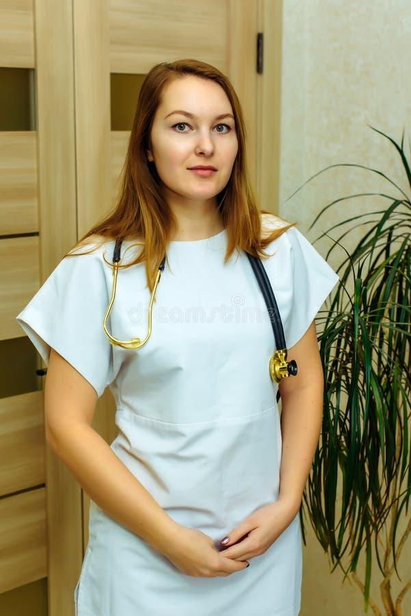 Glimlachende Europese vrouwenarts met stethoscoop in een wit uniform Portret van een jonge medische arbeider met positieve houdin stock fotografie
