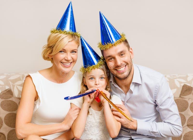 Glimlachende familie in blauwe hoeden die gunsthoornen blazen royalty-vrije stock foto's