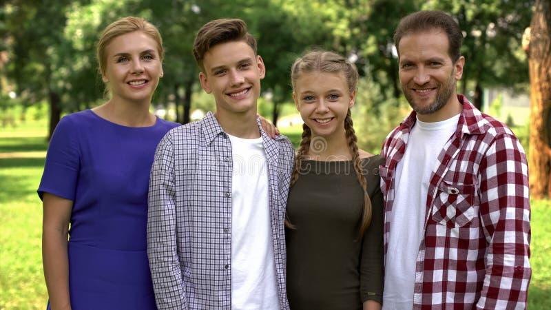 Glimlachende familie die camera, gezondheidszorgkliniek, medische verzekering, therapie bekijken stock afbeeldingen