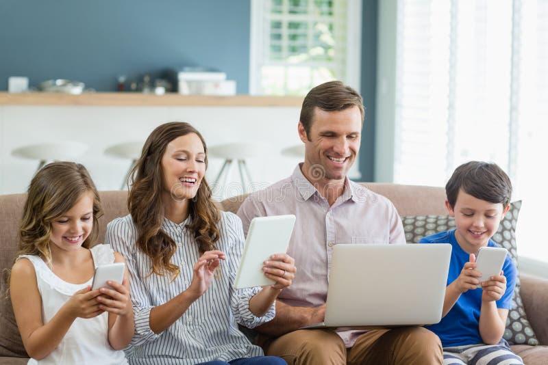 Glimlachende familie die digitale tablet, telefoon en laptop in woonkamer met behulp van royalty-vrije stock fotografie