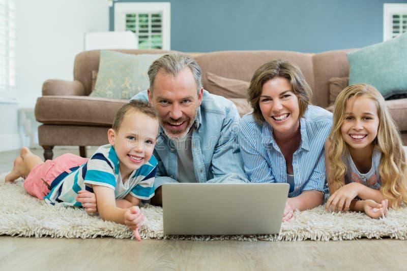 Glimlachende familie die laptop met behulp van terwijl het liggen op tapijt in woonkamer royalty-vrije stock afbeelding