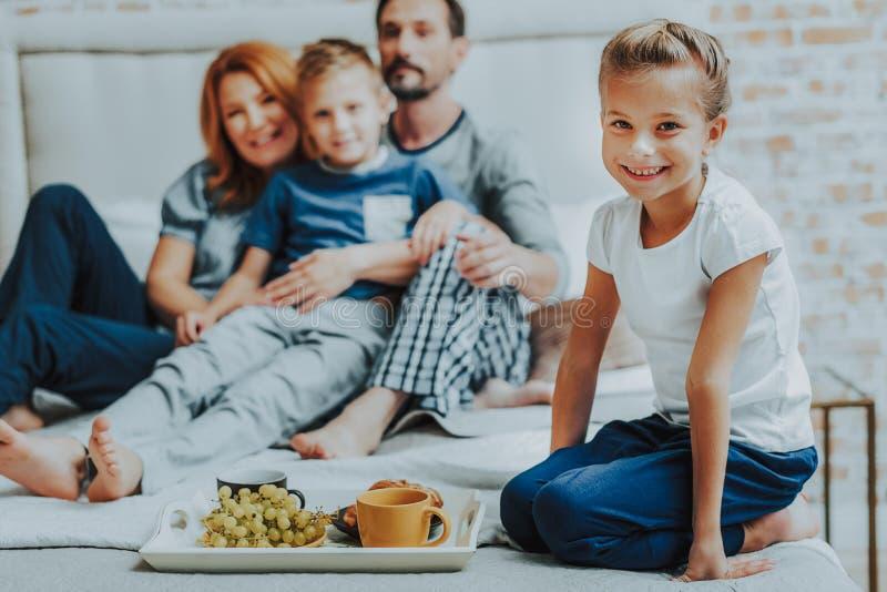 Glimlachende familie die ontbijt samen in bed hebben royalty-vrije stock afbeeldingen