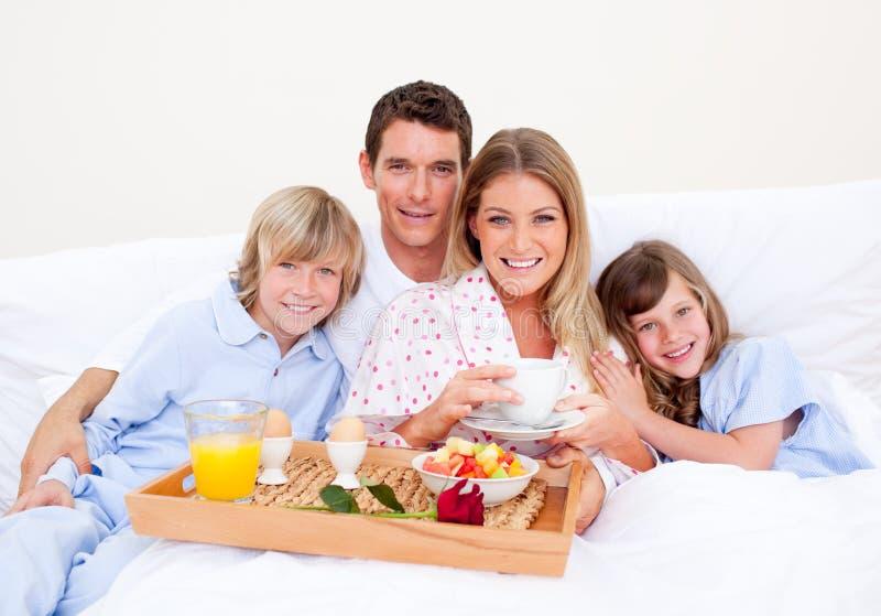 Glimlachende familie die ontbijtzitting op bed heeft stock afbeeldingen