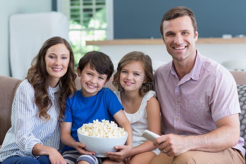 Glimlachende familie die op TV letten en popcorn in woonkamer thuis eten stock fotografie