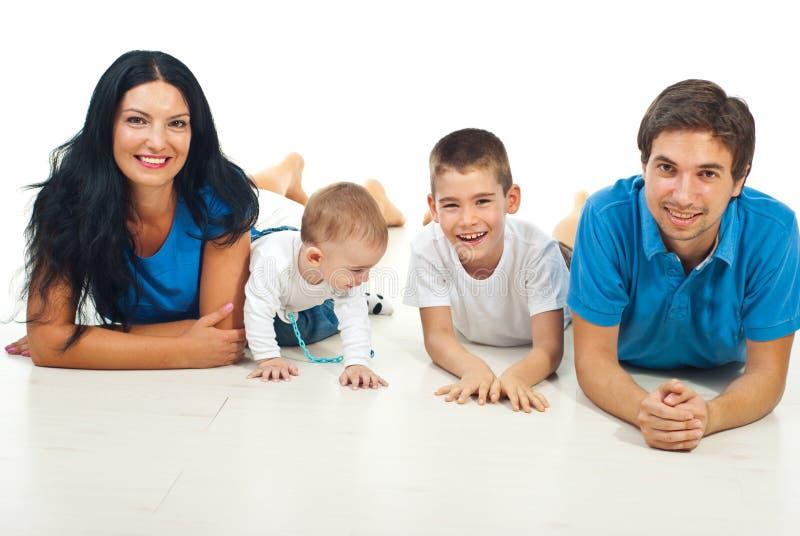 Glimlachende familie die op vloer ligt stock foto