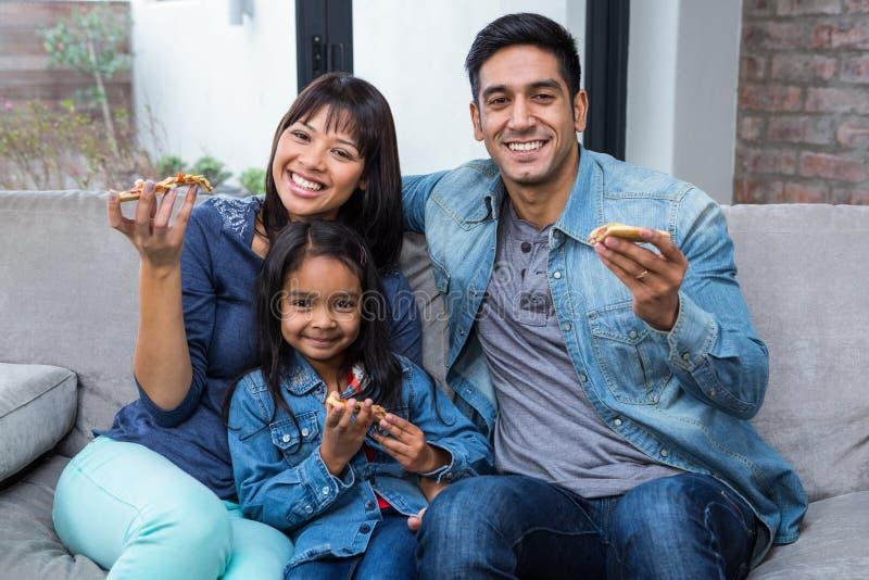 Glimlachende familie die pizza op de bank eten stock afbeeldingen