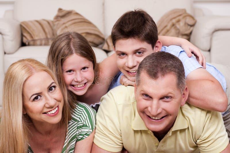 Glimlachende familie die samen op de vloer ligt royalty-vrije stock afbeeldingen