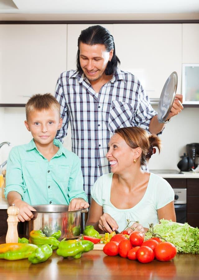 Glimlachende familie kokende groenten stock afbeelding