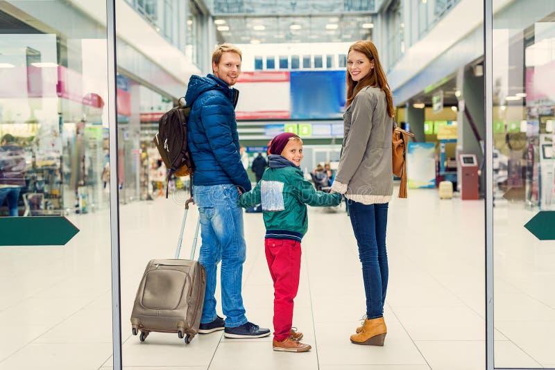 Glimlachende familie met kind bij luchthaven stock fotografie