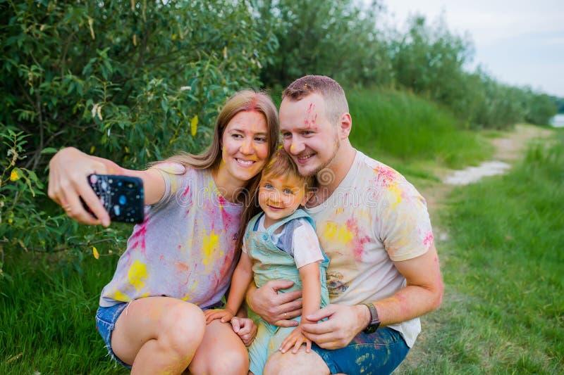 Glimlachende familie in multi-colored verven die selfie op de zomerweide nemen Het portret van de familie royalty-vrije stock afbeelding