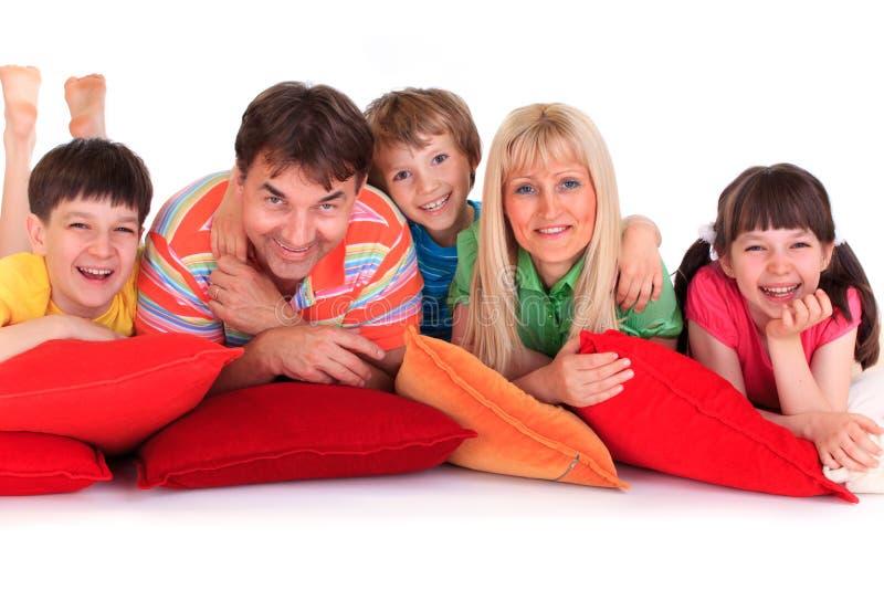 Glimlachende familie op hoofdkussens stock afbeelding