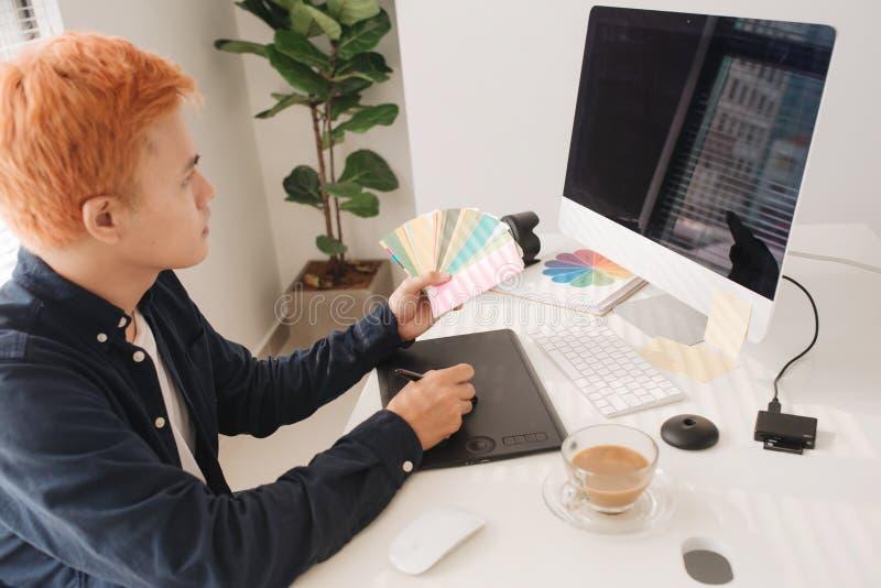 Glimlachende fotoredacteur die aan computer bij bureau met camera werken en royalty-vrije stock foto's