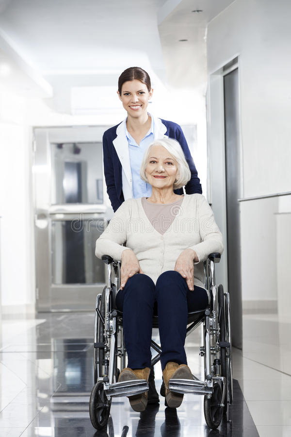 Glimlachende Fysiotherapeut Pushing Senior Woman in Rolstoel royalty-vrije stock afbeeldingen
