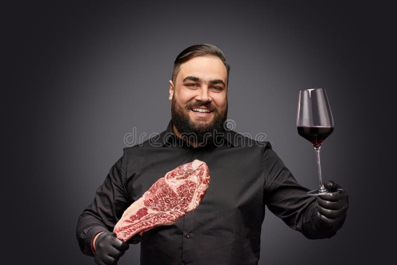 Glimlachende gebaarde chef-kok die vlees en wijn aanbieden stock fotografie