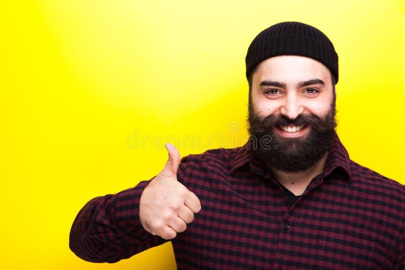 Glimlachende gebaarde hipstermens met zijn omhoog duim stock fotografie
