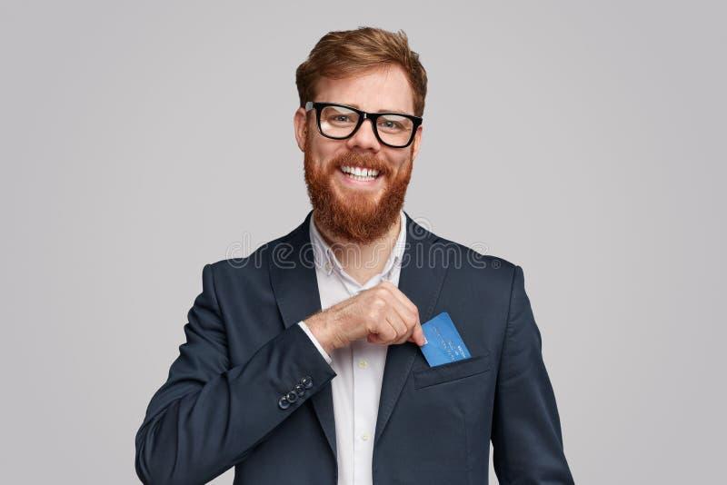 Glimlachende gebaarde mens die creditcard in zak tonen stock fotografie